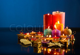 A lot of burning colorful candles against dark blue background