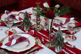 Christmas table with red decoration, napkins, roses, silver, christmas tree and candles