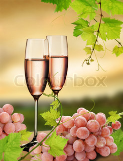 Two glasses of pink champagne with grapes