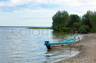 Old wooden fishing boat near the summer lake shore Svityaz, Ukraine