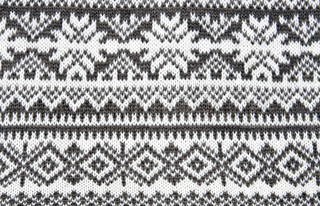 gray background with a knitted pattern to form snowflakes