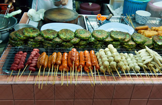 Asian street food tray with skewers, hot dogs