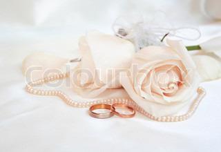 Trauringe und Rosen als Hochzeit-Hintergrund