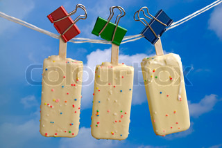 White chocolate ice cream hanging on rope over blue sky