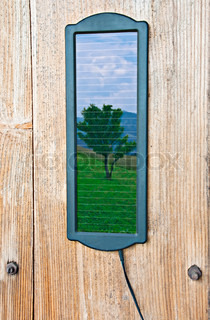 Consept: Using one small solar sell, you save one tree Natural reflection of tree and sky over mountain landscape on solar panel, situated at wooden wall