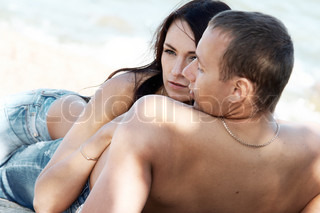 Sensual couple in jeans on a beach