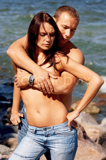 Young couple in blue jeans on a coast