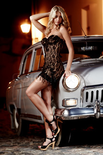 Beautiful lady in black dress standing next to oldtimer car in the night city