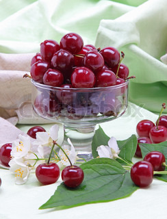 Sweet cherry in glass bowl with flower on linen fabric
