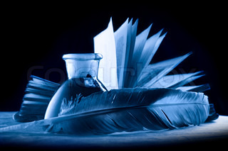 A feather with the bottle full of ink and a book in blue