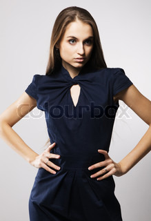 Beautiful fashion model in strict blue dress, gray background