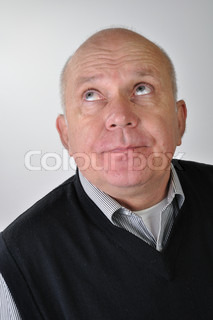 Studio portrait of bald elderly man looking up with funny expression