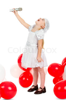 little girl is singing with a microphone, standing next to balloons