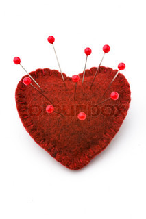 Red heart, studded with a lot of pins, love or health concept, white background
