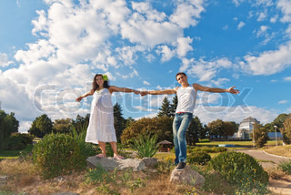 A pregnant woman and her husband hold hands against the background beautiful landscape