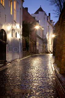 Wet street with old houses at night in Dutch city called Nijmegen