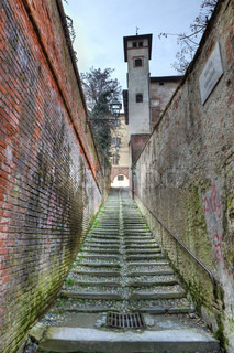 Vertical oriented image of small narrow street among old walls in Saluzzo, northern Italy