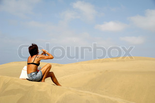 Woman is drinking water in the desert