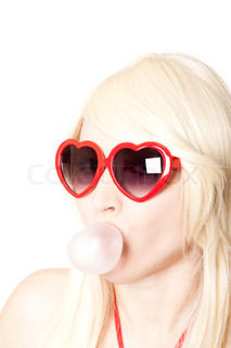 Young sexy blonde in red top wearing heart-shaped glasses making chewing gum bubble, isolated on white