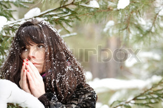 portrait closeup young girl praying on the background of the winter forest
