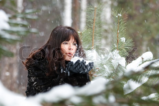portrait of a beautiful young girl with hands in the snow on background of a winter forest