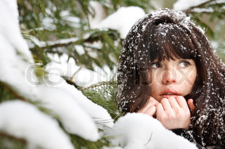 closeup portrait of a young girl on the background of the winter forest