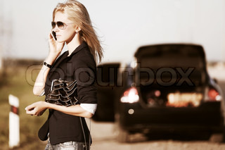 Young woman a broken car calling for help