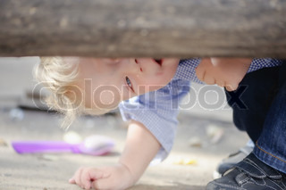 Little boy looking from under the bench, playing hide-and-seek