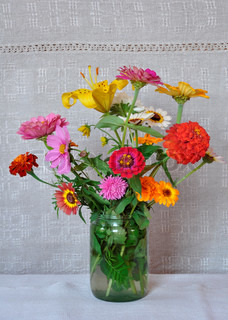 A bouquet of garden flowers in a glass jar on the background of an old linen canvas