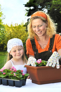 Young mother and her daughter having gardening time