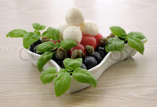 Appetizer of mozzarella, cherry tomatoes and olives, basil and capers