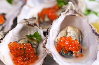 Opened oysters with red caviar