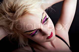 Sexy blonde woman in underwear with creative makeup on black background