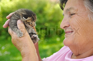 Senior woman holding kleine Katze - outdoor