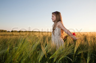 An image of a girl in the field of barley at sunset