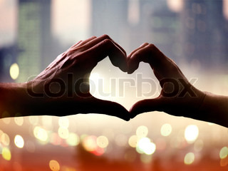 Silhouette of hands in form of heart when sweethearts have touched