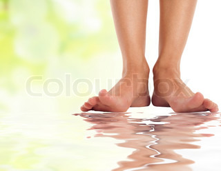 female feet with splayed fingers on water - spa and healthcare concept