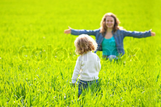 Woman and child playing hide and seek in summer field