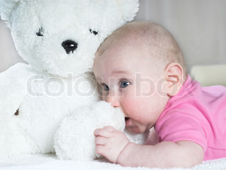 Little baby is playing with teddy bear
