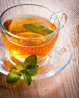 Mint tea in glass cup on wooden table