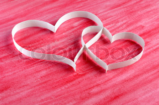 Couple paper hearts on red background