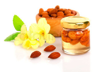 almonds honey with nuts and flowers on a white background
