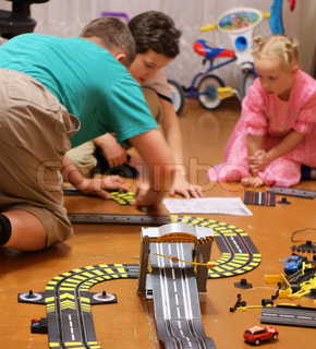 father and children build car race track