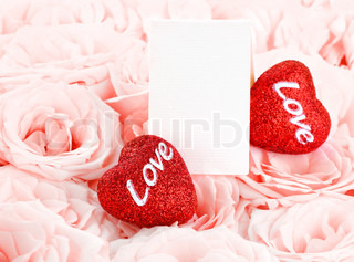 Pink fresh roses background with red hearts & blank greeting card, love concept