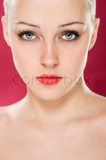 Close-up portrait of beautiful fresh female face with expressive eyes on red background