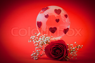 Glass globe with red hearts and a rose. Concept of Valentines day