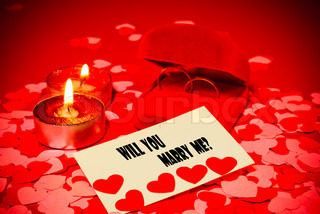 Card with marriage proposal and two rings and two candles over red background