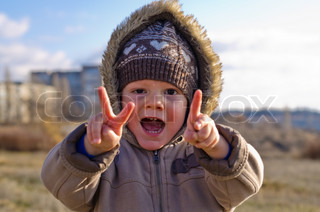 The cheerful little boy on walk shows different figures fingers in the autumn, laughs