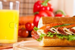 big sandwich with fresh vegetables and juice on wooden board