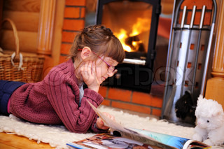 Child girl is reading a book in front of fireplace